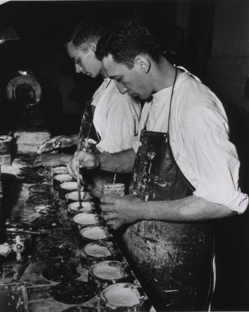 <p>Interior view: work table with faucet, container covers, and  open containers; two men wearing aprons over dental gowns are working at the table, one is holding a glass jar.</p>