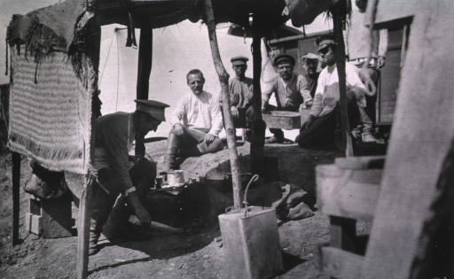 <p>Soldiers(?) sit around the outside kitchen of a medical supply depot train.</p>