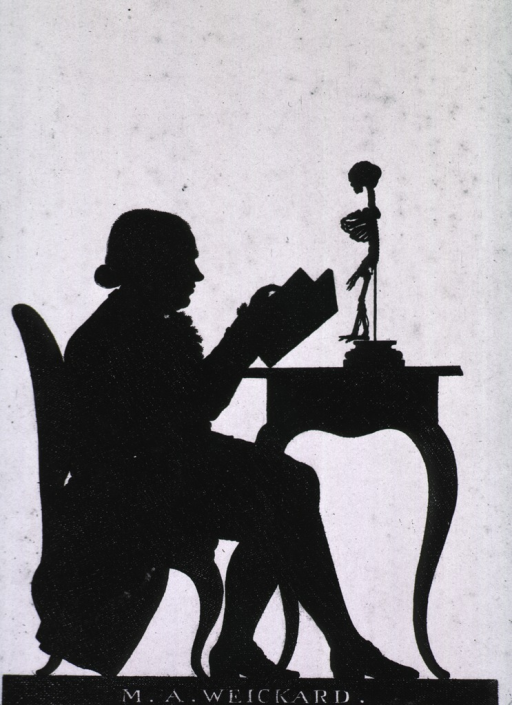 <p>Seated, full figure, right profile.  Reading; skeleton of child on table.</p>