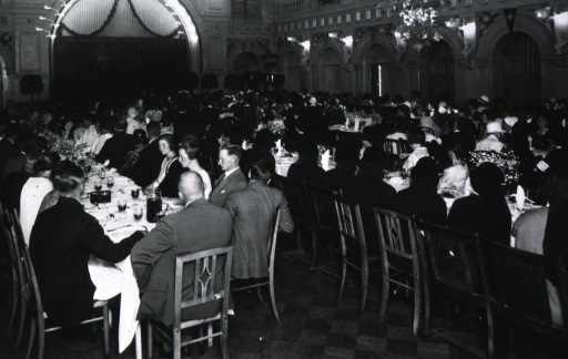<p>Showing the interior of a large hall filled with quests at a luncheon sponsored by the National League of Trained Nurses of Finland.</p>