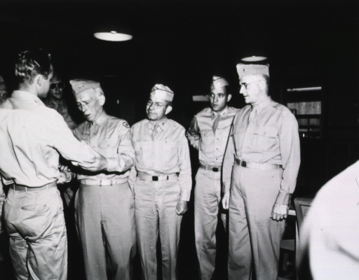 <p>General Kirk greets another man at the 129th Station Hospital in Hawaii, while several other men in military uniform look on.</p>