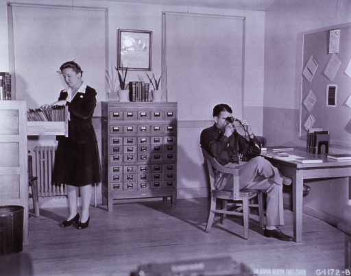 <p>Librarian looks through vertical file while patron examines microfilm.</p>