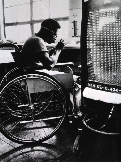 <p>A man sitting in a wheelchair is learning how to repair watches.</p>