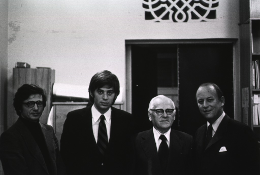 <p>Dr. Donald S. Fredrickson, director of the National Institutes of Health, is standing next to Academician Alexander A. Bayev, of the USSR Academy of Sciences.  Dr. Scriabin is standing with them in front of a doorway at the USSR Academy of Sciences Institute of Molecular Biology.  There are bookshelves behind Dr. Fredrickson.</p>