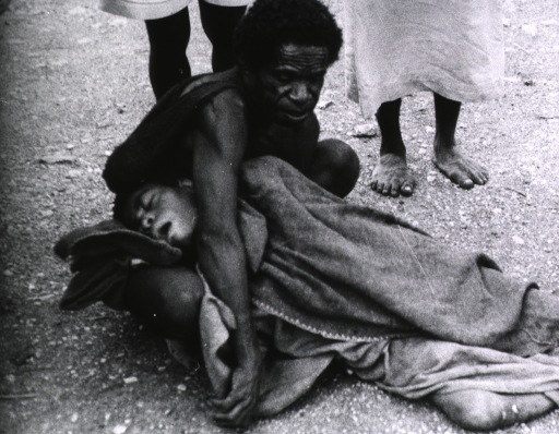 <p>A man is holding the body of a young man that has died from kuru, a fatal nervous system disorder. They are members of the Fore, a primitive tribe living in the Eastern Highlands of New Guinea.</p>