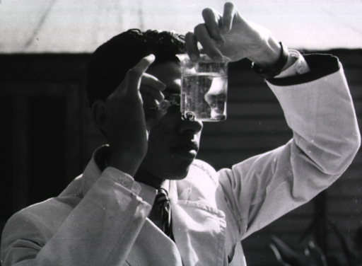 <p>A man is holding a beaker of water close to his face and looking through it using a magnifying glass.</p>