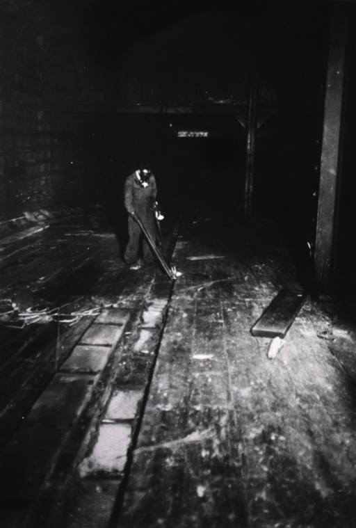 <p>View of U.S. Public Health Service worker (?) in gas-mask and coveralls spraying hydrogen cyanide beneath the floorboards in the hull of a ship during a visit by League of Nations fumigation experts to the New York Quarantine Station.</p>