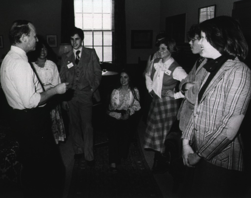 <p>A girl is sitting with four girls and two boys standing.  They are  listening to Dr. Donald S. Fredrickson, director of the National Institutes of Health.  Pictures are on the walls.  There is a round table under a window.  The floor is carpeted with a runner over it.</p>
