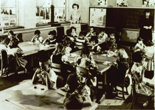 <p>Interior view: several children sitting around tables and two teachers stand in a classroom; each child is holding a small bottle to their mouth, and has a tissue and a bottle cap in front on him/her.</p>