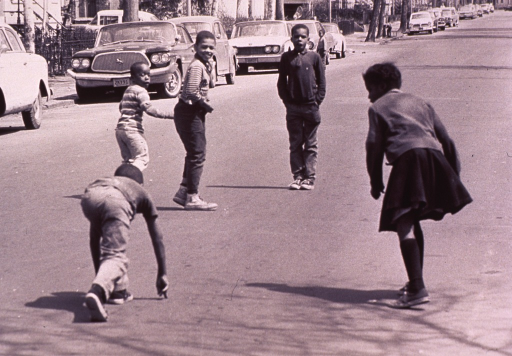 <p>Children are getting ready to have a foot race in the street.</p>