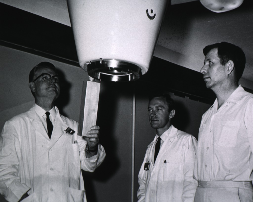 <p>Half length, turned slightly to right, looking upward; wearing lab coat; wearing glasses; standing, holding a linear accelerator; two other men look on.</p>