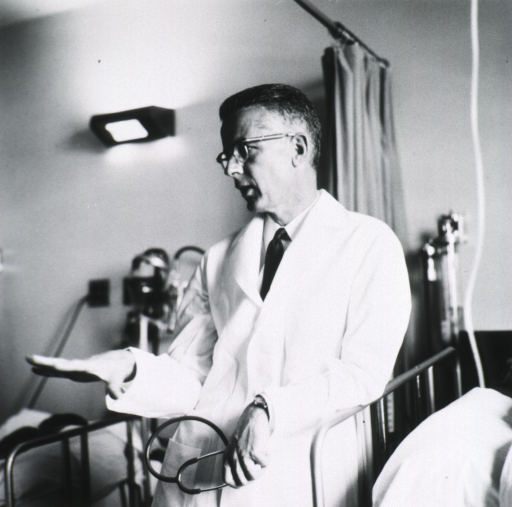 <p>Half-length, left pose, standing at end of patient's bed; wearing glasses and white lab coat; holding stethoscope; gesturing with left hand.</p>