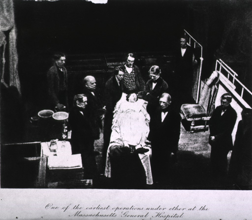 <p>Fully dressed female patient lying on the operating table, surrounded by the surgeons of Mass. Gen. Hosp., incl. John Collins Warren.</p>