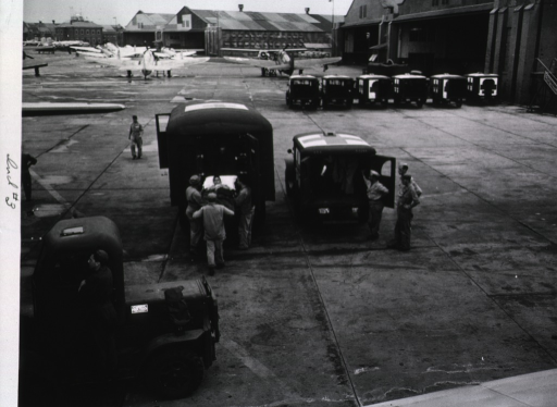 <p>The airstrip of an unidentified military base is shown from above.  In the foreground servicemen lift a wounded serviceman who lies on a stretcher into the opened back door of an ambulance.  In the background a row of ambulances stands at the ready next to open hangars and a group of airplanes.</p>