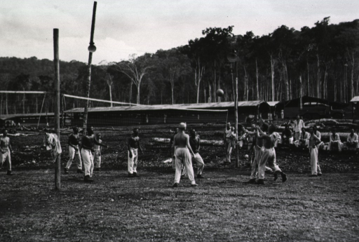 <p>Shirtless servicemen play volleyball on a field while other men sit or stand and watch.</p>