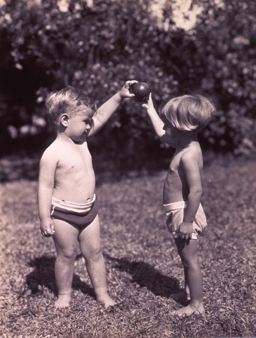 <p>A little boy and a little girl are facing each other and holding a small ball between them.</p>