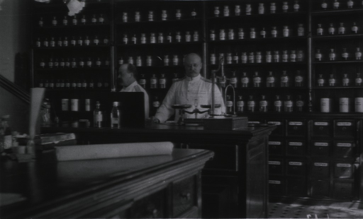 <p>An interior view of the dispensary at the Naval Hospital.  Two staff people stand behind the counter.</p>