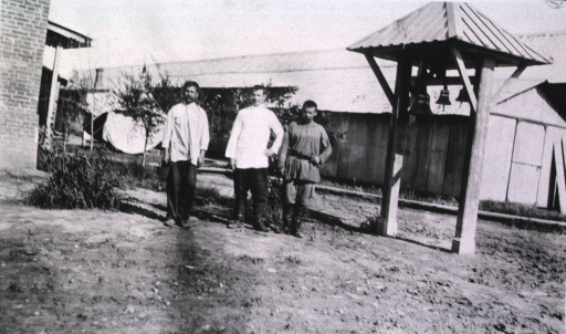 <p>Three hospital workers(?) stand near the Chapel bells of the Kaufman No. 2 Red Cross Hospital.</p>