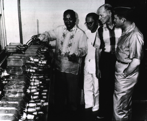 <p>Interior of a Philippine government laboratory: Philippine and American officials examine a shipment of bottles of anti-cholera vaccine destined for Thailand.</p>