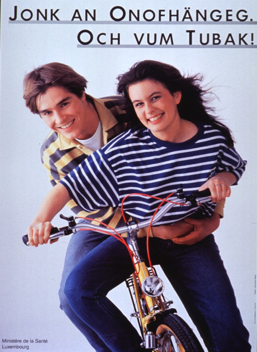 <p>Poster is a reproduction of a color photo.  Title at top of poster.  Visual image is a young woman getting ready to ride a bike, with a young man behind her hanging on as a passenger.</p>