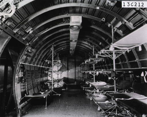 <p>The interior of the cabin of a plane is shown from the rear.  On either side a row of empty litters are stacked (cf. no. 23).</p>