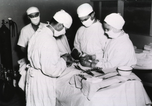 <p>A surgeon, anesthetist, technician, and nurse participate in the removal of shrapnel from a Leyte casualty.</p>