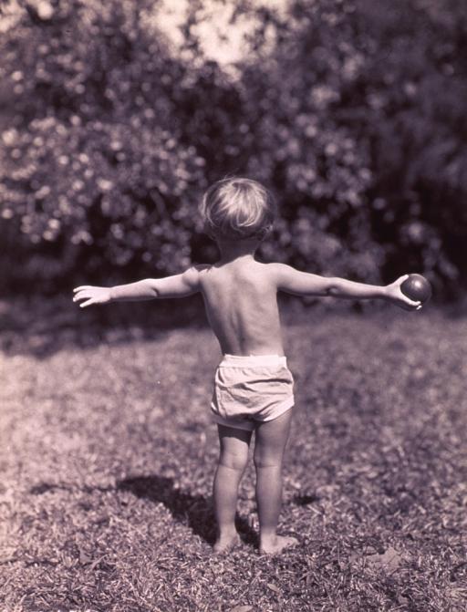 <p>View from behind of a little girl standing with her arms outstretched; she is holding a ball in her right hand.</p>