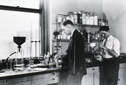 <p>Three-quarter length, standing at laboratory table.</p>