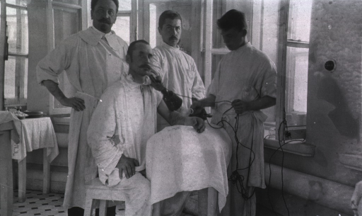 <p>Three members of the medical staff attend a patient in the surgical dressing room of the Naval Hospital.</p>
