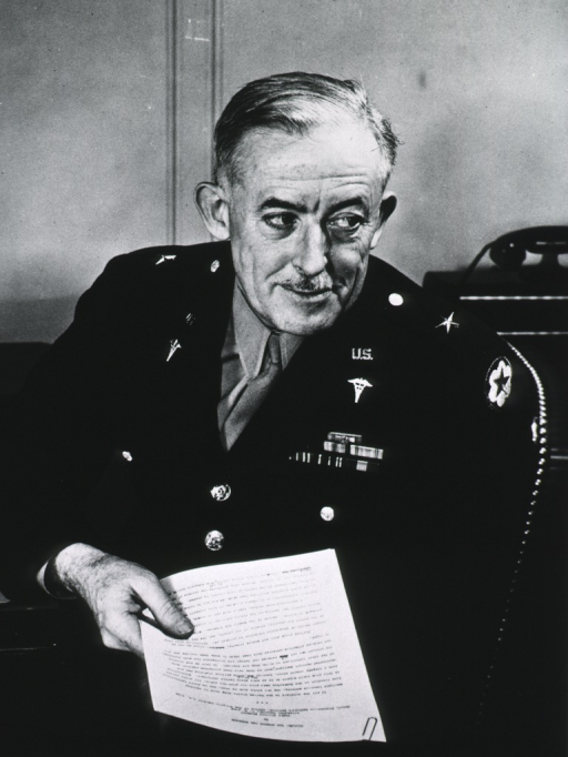 <p>Seated at desk, full face, holding paper, uniform, brig.-gen.</p>