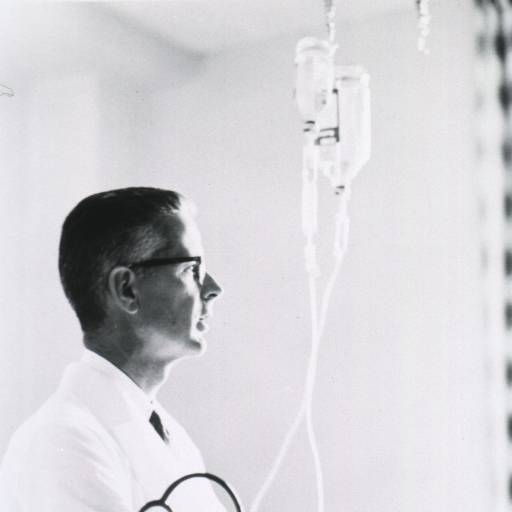 <p>Head and shoulders, right profile; wearing glasses and white lab coat; examining intravenous apparatus.</p>
