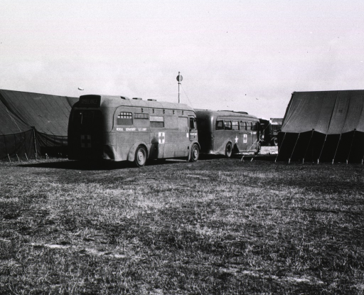 <p>Two ambulance buses emblazoned with the logo of the U.S. Army's Medical Department, are parked one in front of the other between tents pitched on a grassy field.</p>