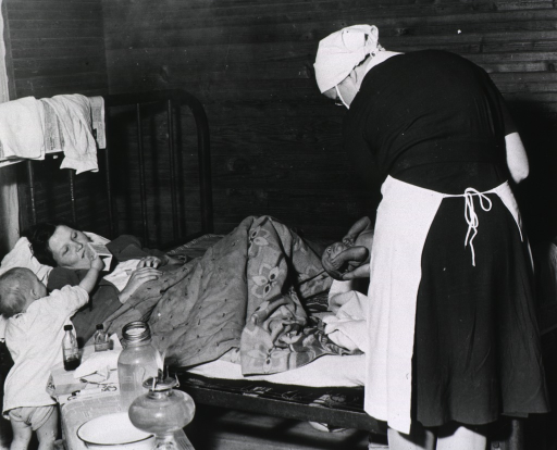 <p>A woman lying on a bed has just given birth; a nurse-midwife stands at the foot of the bed holding the newborn; a small child holds a box near the woman's face; among the items on a bench near the bed is an oil lamp with an open flame.</p>
