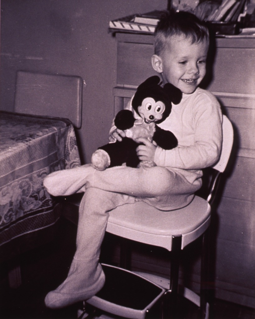 <p>A little boy is sitting on a stool holding a Mickey Mouse doll.</p>