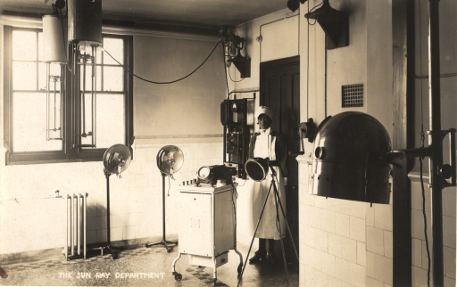 <p>Postcard featuring a black and white photograph of a nurse standing in the sun ray department in a hospital. The room has equipment both on the floor and ceiling.</p>