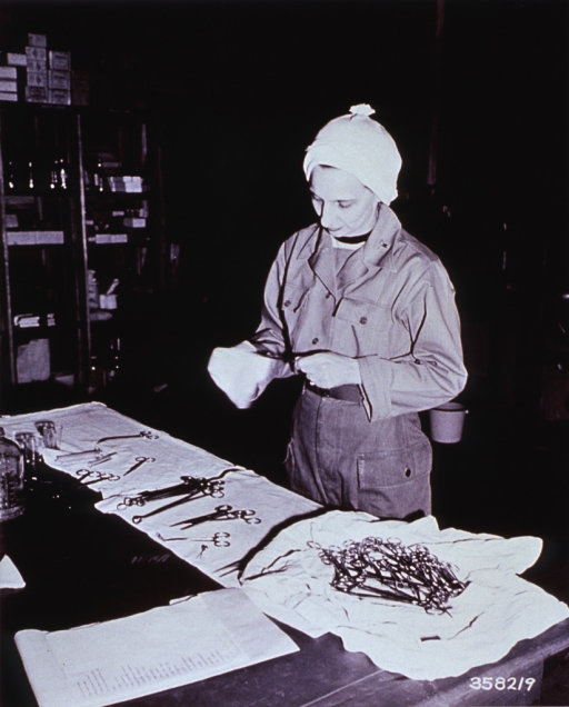 <p>Operating room nurse preparing instruments for surgery at the 3rd Station Hospital, Korea.</p>