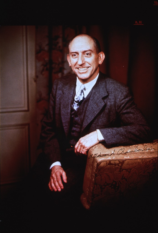 <p>Three-quarter length, seated on arm of chair, left pose, arm over back of chair.</p>
