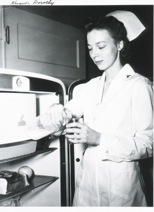 <p>Three-quarter length, standing at open refrigerator, left pose; wearing nurses uniform and cap; pouring milk.</p>