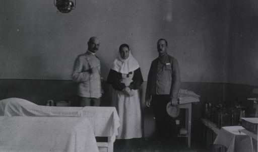 <p>A nurse and two surgeons(?) in the operating room at the Kaufman No. 2 Red Cross Hospital.</p>