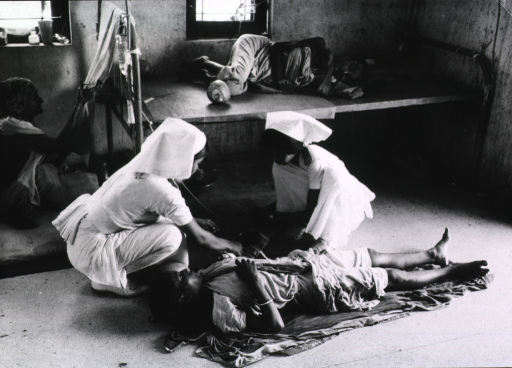 <p>Interior view: two nurses attach an intravenous drip containing rehydration fluids to a female patient lying on the floor; two other female patients are present.</p>