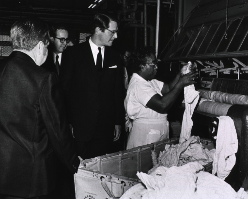 <p>Elliot Richardson and Clinical Center Executive Officer Earl Laurence observe NIH laundry operations during Richardson's visit on March 16, 1971.</p>