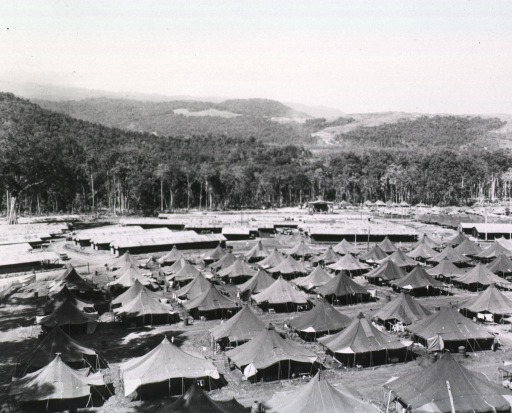<p>Aerial view shows a complex of tents and buildings erected on a field.  Mountains rise in the distance.</p>