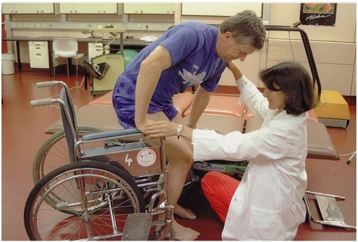 A man is standing up from a wheelchair (Stark, 1998).