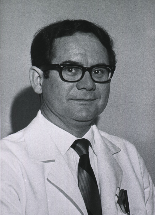 <p>Head and shoulders, turned slightly to right; wearing lab coat and glasses.</p>