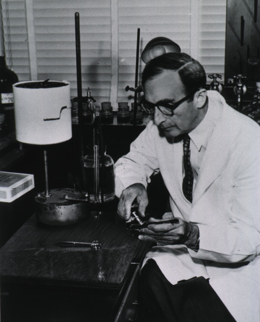 <p>Seated at table in laboratory; wearing white lab coat; holding instruments.</p>
