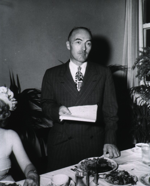 <p>Half-length, standing at banquet table, full face; holding papers.</p>
