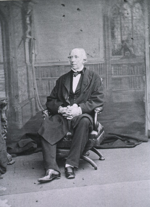 <p>Seated with hands folded, left pose; backdrop of bookshelves and stained glass window.</p>