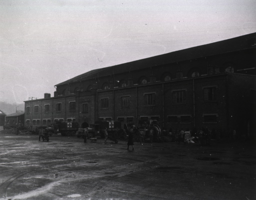<p>Men at work outside a three-story building.  Several Army ambulances are parked in front of the building.</p>