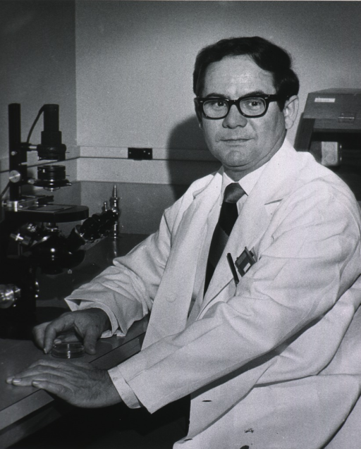 <p>Three-quarters length, full face; wearing lab coat and glasses; seated at microscope, holding petri dish.</p>