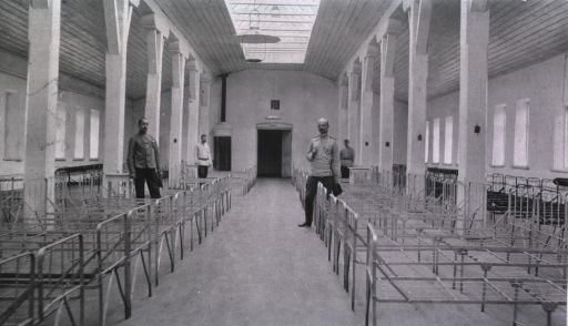 <p>Four medical personnel in a ward at the Kaufman No. 2 Red Cross Hospital.  Only bed frames are in the room.</p>
